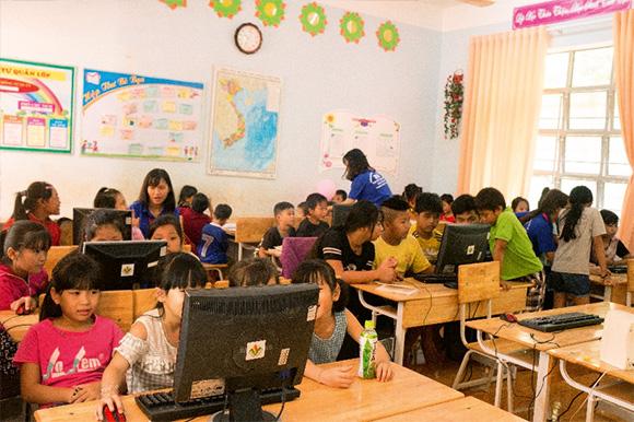 Các tình nguyện viên tận tình hướng dẫn các em thực hành trong một lớp học hè về tin học